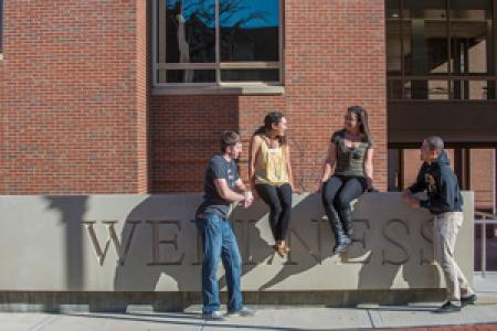 Photo of students hanging around the Wellness wall outside of UHS
