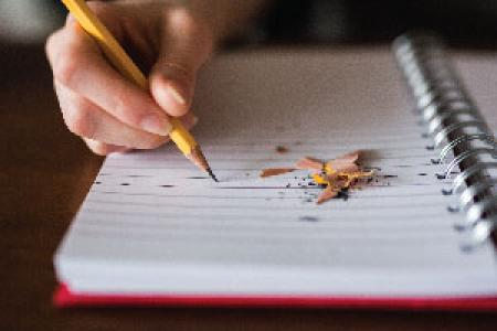 Photo of person writing in notebook
